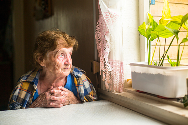 Lonely old woman sitting by the window in her cottage.