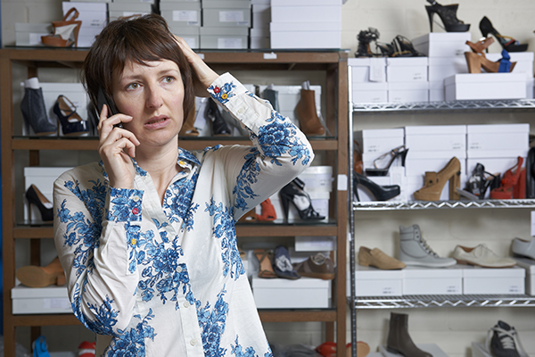 Worried Owner Of Shoe Store On Phone