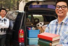 Student unpacking books from car