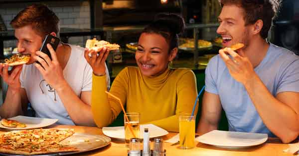 Three young adults eating pizza